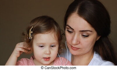 Mother and daughter in headphones look at the screen of the smartphone. Mom and child communicate by video link.