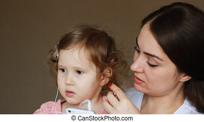 Mother and daughter in headphones look at the screen of the...