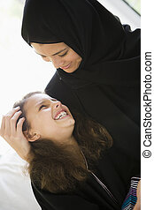 Mother and daughter in living room smiling (high...