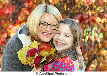 mother and daughter in park autumn season