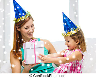 mother and daughter in party hats with gift box