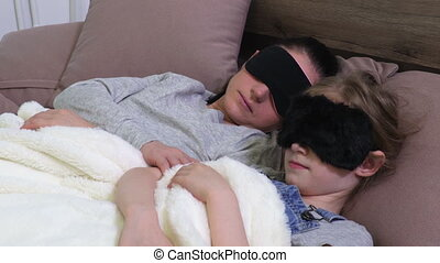 Mother and daughter in sleeping masks in bed