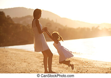 mother and daughter  in the beach at sunset happy