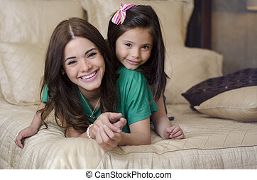 Mother and daughter in the bedroom - Portrait of young...