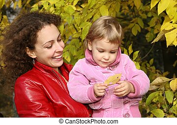 mother and daughter in the park in autumn 2