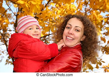 mother and daughter in the park in autumn