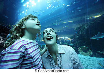 mother and daughter in underwater aquarium tunnel, amazement faces, wide angle