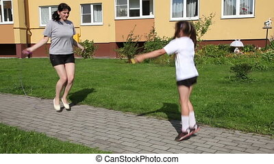 mother and daughter jumping with ro