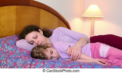 Mother and daughter lay on bed and try to sleep