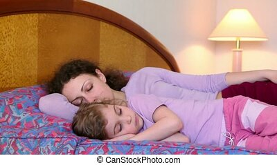 Mother and her little daughter lay on bed, mom sleeps but girl does not