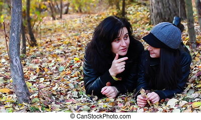 Mother and daughter layed on leaves