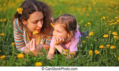 Mother and daughter lie on lawn with flowers in hair