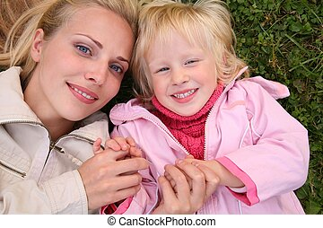 mother and daughter lie on the grass and look upward 2