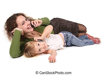 mother and daughter lie they talk on the cell phones on the...
