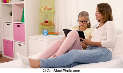 mother and daughter listen to music on tablet pc - people,...