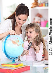 Mother and daughter looking at a globe with a magnifying glass