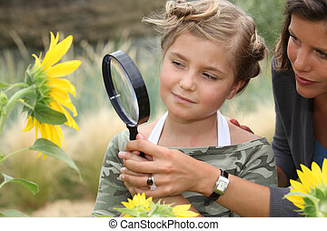 Mother and daughter looking at a sunflower with a magnifying glass
