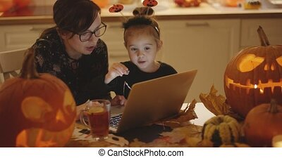 Mother and daughter looking at laptop screen - Woman and her...