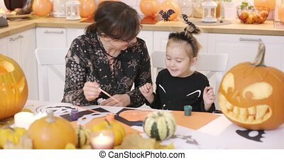 Mother and daughter looking at painted pumpkin - Mother and...