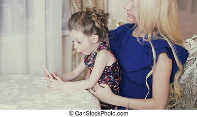 Mother and daughter looking at photos of the smartphone