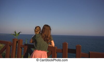 Mother and daughter looking at sea - Young woman in casual...