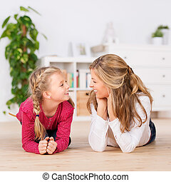 Mother And Daughter Lying Comfortably On Floor