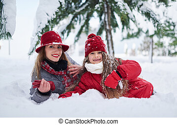 Mother and daughter lying in snowdrift and looking at...