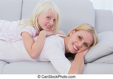 Mother and daughter lying on couch