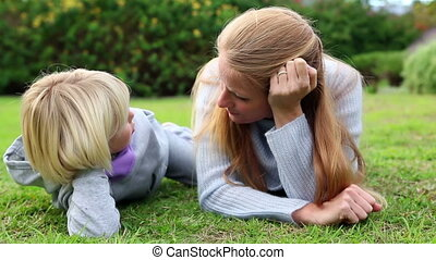 Mother and daughter lying on grass talking at home in garden