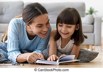 Mother and daughter lying on warm floor reading book
