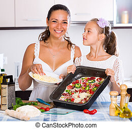 Mother and daughter making pizza - Beautiful little girl ...