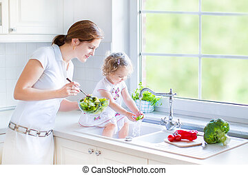 Mother and daughter making salad - Young mother and her...