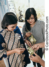 making traditional ketupat or rice cake - mother and...