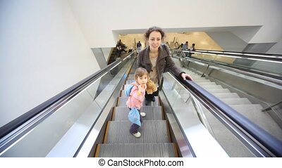 mother and daughter moving up on escalator - happy young...