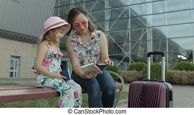 Mother and little daughter sitting on bench outdoors near international airport terminal with suitcase luggage on wheels. Woman hold passports and tickets in hand. Child girl and mom tourism, vacation