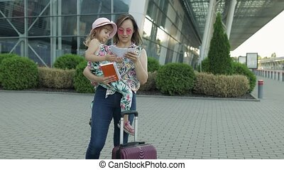 Mother and little daughter stay outdoors near international airport terminal with suitcase luggage on wheels. Woman hold passports and tickets in hand. Child girl and mom tourism, vacation concept