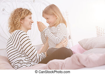 Mother and daughter on a bed