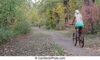 Mother and daughter on a bicycle in autumn forest