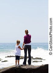 mother and daughter on beach - Rear view of a mother and...