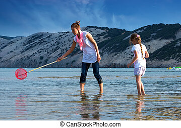 Mother and daughter on the beach fishing