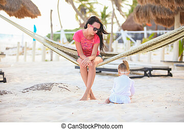 Mother and daughter on tropical vacation relaxing in hammock