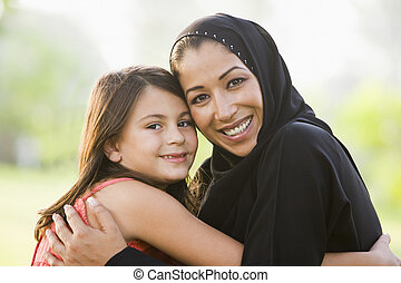 Mother and daughter outdoors in park embracing and smiling (selective focus)