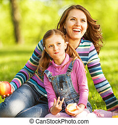 mother and daughter outdoors on a picnic eat apple