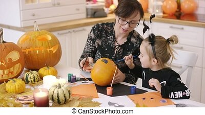 Mother and daughter painting face on pumpkin - Mother and...