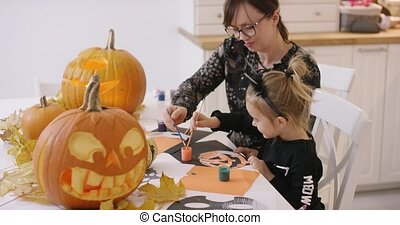 Mother and daughter painting jack-o-lantern - Woman in...