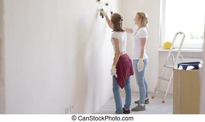 Mother and daughter painting wall
