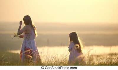 Mother and daughter picking flowers to weave wreath on the...
