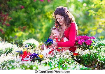 Mother and daughter planting flowers - Happy family, young...