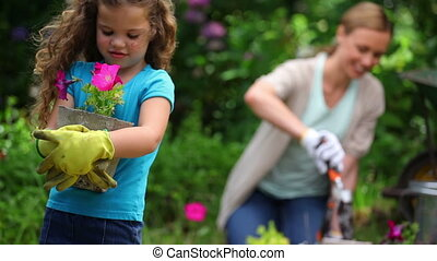Mother and daughter planting flowers in a garden