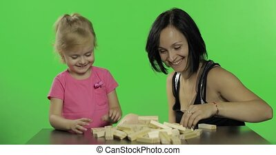 Mother and daughter play. Child making a tower from wooden...